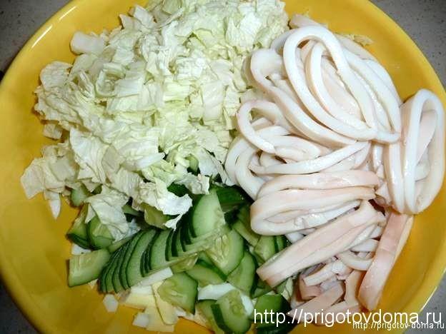 Кальмары нарезать кольцами и сложить в салатник