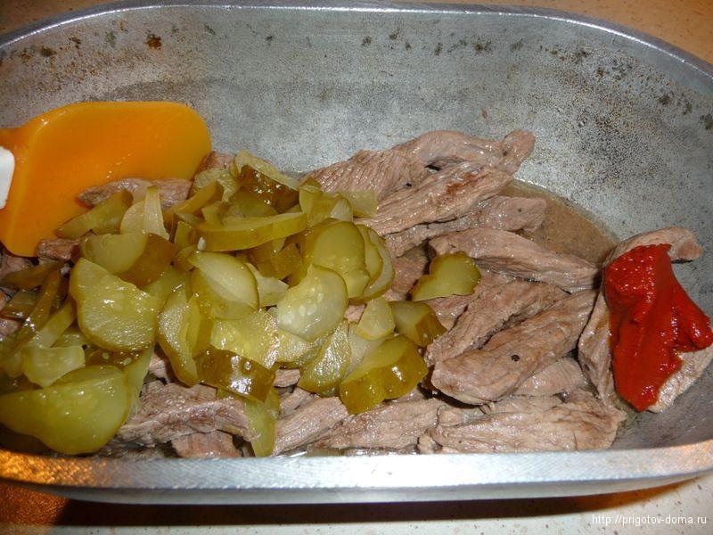 добавляем к мясу огурцы и томатную пасту