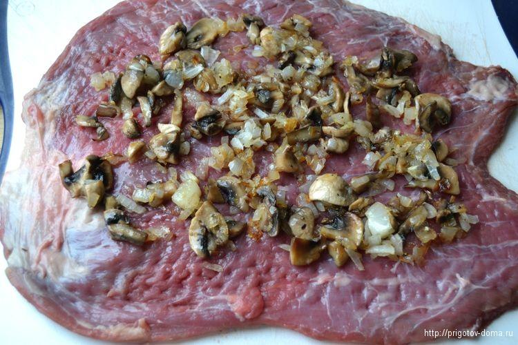 на мясо выкладываем лук с грибами