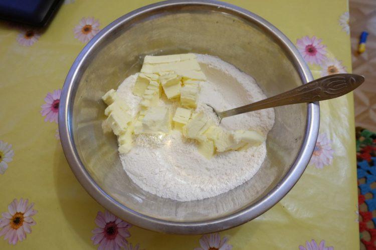 Сливочное масло нарезаем небольшими кусочками и добавляем в муку